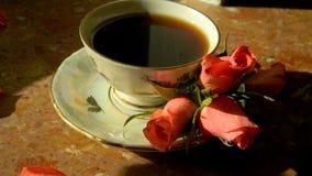 Une tasse de café avec des roses sur une soucoupe Photo stock