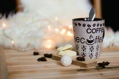 Une tasse de café avec du cacao sur le fond de lumières de Noël Image libre de droits