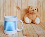 Une tasse de café avec l'ours de nounours et le fond en bois Type de cru Photo libre de droits