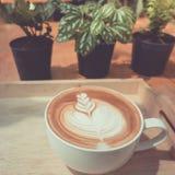 Une tasse de café avec le modèle de coeur dans une tasse blanche Photo libre de droits