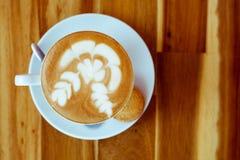 Une tasse de café avec le modèle dans une tasse blanche avec le biscuit sur le fond en bois Photographie stock