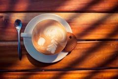 Une tasse de café avec le modèle dans une tasse blanche avec le biscuit sur le fond en bois Photo stock
