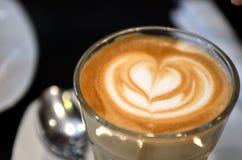 Une tasse de café avec le modèle de coeur dans une tasse blanche Photos stock