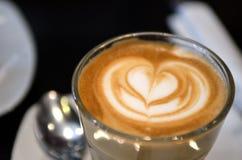 Une tasse de café avec le modèle de coeur dans une tasse blanche Image stock