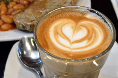 Une tasse de café avec le modèle de coeur dans une tasse blanche Image libre de droits