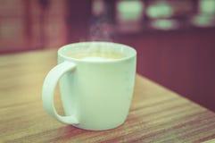 Une tasse de café avec le modèle de coeur dans une tasse blanche sur le dos en bois Photo stock