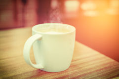 Une tasse de café avec le modèle de coeur dans une tasse blanche sur le dos en bois Image libre de droits