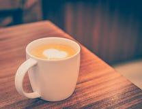 Une tasse de café avec le modèle de coeur dans une tasse blanche sur le dos en bois Photo libre de droits