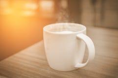 Une tasse de café avec le modèle de coeur dans une tasse blanche sur le dos en bois Photographie stock