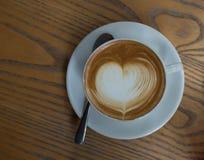Une tasse de café avec le modèle de coeur dans une tasse blanche sur le dos en bois Photos stock