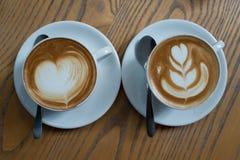 Une tasse de café avec le modèle de coeur dans une tasse blanche sur le dos en bois Images libres de droits