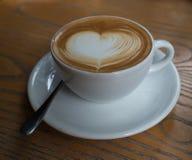 Une tasse de café avec le modèle de coeur dans une tasse blanche sur le dos en bois Photographie stock libre de droits