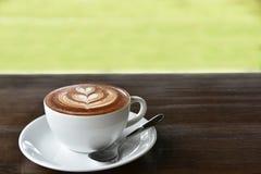 Une tasse de café avec le modèle de coeur dans une tasse blanche sur le dos en bois Photos libres de droits