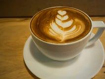 Une tasse de café avec le modèle de coeur dans une tasse blanche sur le tabl en bois Image libre de droits