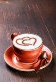 Une tasse de café avec le modèle de coeur sur le fond en bois images libres de droits