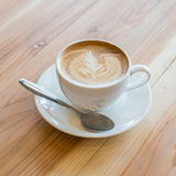 Une tasse de café avec le modèle de feuille dans une tasse blanche Images libres de droits