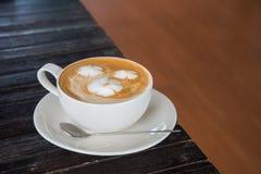 Une tasse de café avec le modèle de fleur dans une tasse blanche sur le CCB en bois Image stock