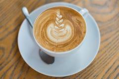 Une tasse de café avec le modèle de fleur dans une tasse blanche sur le fond en bois Images stock