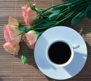 Une tasse de café avec les fleurs roses sur le fond en bambou Images libres de droits
