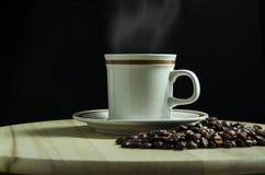 Une tasse de café avec les grains de café photo stock