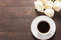Une tasse de café avec les roses blanches sur le fond en bois Photo stock