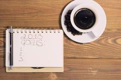 Une tasse de café avec un carnet sur un fond en bois Photos libres de droits