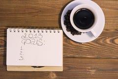 Une tasse de café avec un carnet sur un fond en bois Image stock