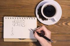 Une tasse de café avec un carnet sur un fond en bois Image libre de droits