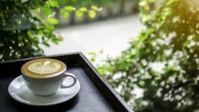 Une tasse de café chaud avec l'art de lait près du vitrail voient dehors photos libres de droits