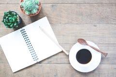 Une tasse de café chaud avec le carnet et le pot vides du cactus sur la table en bois Photographie stock