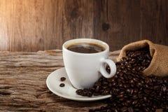 Une tasse de café chaud sur une table en bois avec les grains de café rôtis Photographie stock