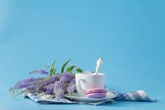 Une tasse de café d'americano de matin avec les macarons français sur le bleu Photographie stock libre de droits