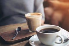 Une tasse de café d'Americano et d'un verre de café de latte sur la table en bois de vintage en café Photos stock