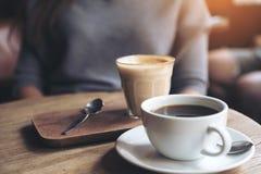Une tasse de café d'Americano et d'un verre de café de latte sur la table en bois de vintage en café Photo stock