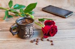 Une tasse de café, d'une rose rouge et d'un smartphone sur une table en bois Photographie stock