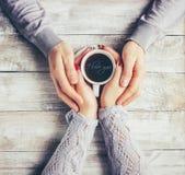 Une tasse de café dans les mains des amants Silhouette dans une tasse Photographie stock libre de droits