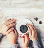 Une tasse de café dans les mains des amants Silhouette dans une tasse Photographie stock