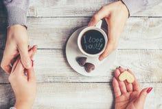 Une tasse de café dans les mains des amants Silhouette dans une tasse Photo stock