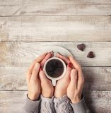 Une tasse de café dans les mains des amants Silhouette dans une tasse Photos stock