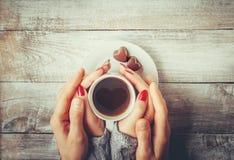 Une tasse de café dans les mains des amants Silhouette dans une tasse Images stock