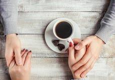Une tasse de café dans les mains des amants Silhouette dans une tasse Photo libre de droits