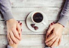 Une tasse de café dans les mains des amants Silhouette dans une tasse Images libres de droits