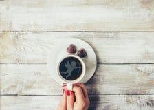 Une tasse de café dans les mains des amants Silhouette dans une tasse Image libre de droits