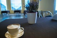 Une tasse de café dans un café avec un fond brouillé Photographie stock libre de droits