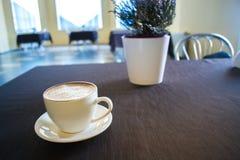 Une tasse de café dans un café avec un fond brouillé Photos libres de droits