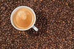 Une tasse de café dans un groupe de grains de café Images stock