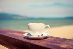 Une tasse de café dans une tasse blanche sur le fond de plage Photographie stock