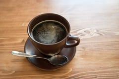 Une tasse de café dans une tasse brune sur le fond en bois Photographie stock