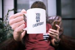 Une tasse de café de prise de type avec le mot vous êtes mon smartphone quotidien et jouant Photos stock