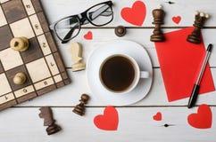 Une tasse de café, de verres et de pièces d'échecs sur une table en bois, dessus Photographie stock libre de droits